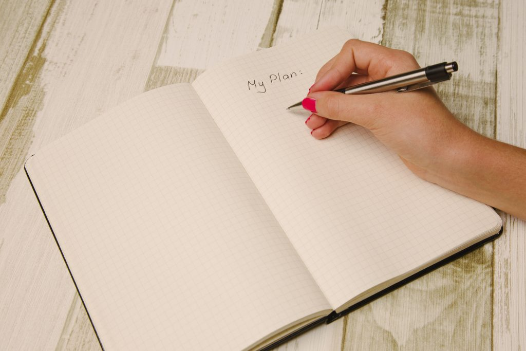 Female hand holding a pen and writing a plan in a planner for planning a digital job ad.
